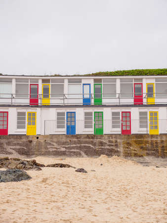 Wide vertical view of multiple seaside apartments with colorful doors along Porthgwidden beach on a cloudy day. St. Ives, England. Travel and tourism.