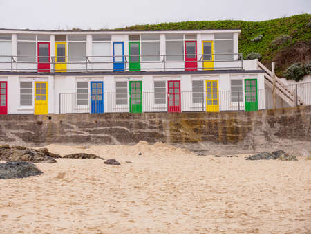 Wide angle view of multiple seaside apartments with colorful doors along Porthgwidden beach on a cloudy day. St. Ives, England. Travel and tourism. Stock Photo