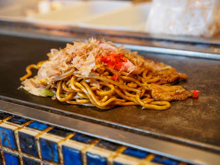 Closeup detail of a freshly cooked Yakisoba topped with Katsuobushi fish flakes, sauce, and ginger, on a Teppan grill. Shallow focus. Dotonbori, Osaka, Japan. Travel and cuisine. Stock Photo