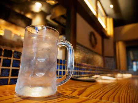 Wide closeup of a empty beer stein mug, cold with condensation, at an Izakaya Okonomiyaki pizza bar. Namba, Osaka, Japan. Travel and cuisine.