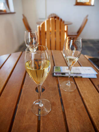 Wide closeup of glasses of sparkling white wines on a wooden table during a tasting session at a winery. Vertical orientation. Nanstallon, Bodmin, England. Travel and Cornish wine industry.