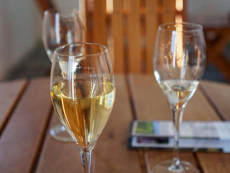 Closeup detail of multiple glasses of sparkling and white wines on a wooden table during a tasting session at a winery. Nanstallon, Bodmin, England. Travel and Cornish wine industry. Stock Photo