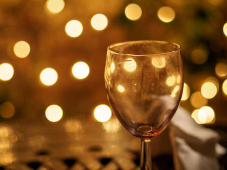 Closeup detail of an empty wine glass reflecting beautiful yellow lights of a pub in the background. Shallow Bokeh focus. London, England. Party and night life.