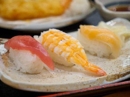 Closeup macro detail of a Sushi platter of Maguro bluefin tuna, Ebi shrimp, and salmon. Narita, Chiba, Japan. Travel and traditional Sashimi cuisine.