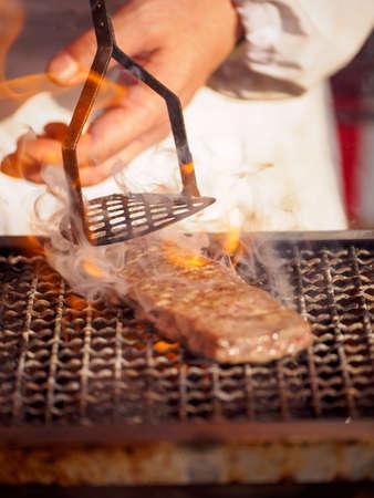 Chef roasts a beef skewer, Yakiniku Kushiyaki, using a meat press over a flaming charcoal grill. Vertical orientation. Omiya, Saitama, Japan. Travel and street food. Stock Photo