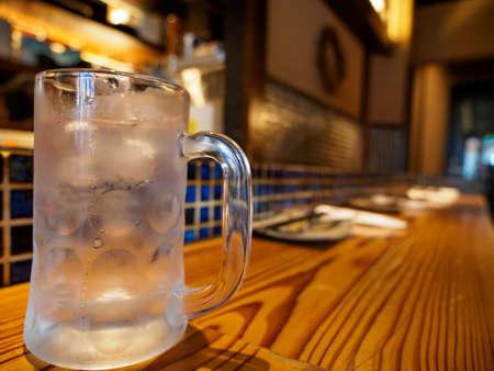 Wide closeup of a empty beer mug with condensation on a wooden counter at an Izakaya bar. Namba, Osaka, Japan. Travel and cuisine.