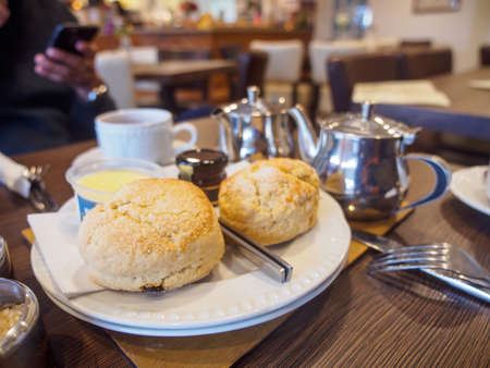 Wide closeup of freshly-baked scones with clotted cream and jam at a restaurant during afternoon tea. Tintagel, England. Travel and Cornish cuisine. Stock Photo