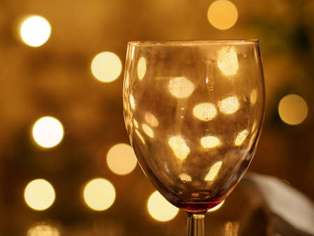 Closeup macro detail of an empty wine glass reflecting beautiful yellow lights in the background. Shallow Bokeh focus. London, England. Party and night life. Stock Photo