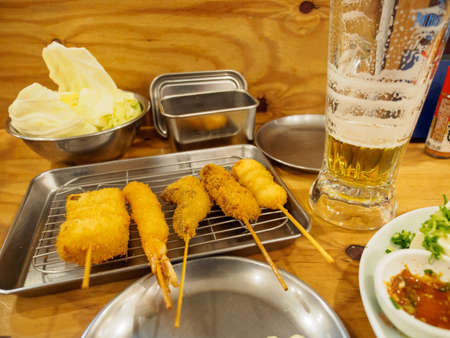 Wide closeup of multiple Kushikatsu, batter-fried skewers from Osaka also known as Kushiage, served with beer and cold tofu at a Izakaya pub. Tokyo, Japan. Travel and cuisine.