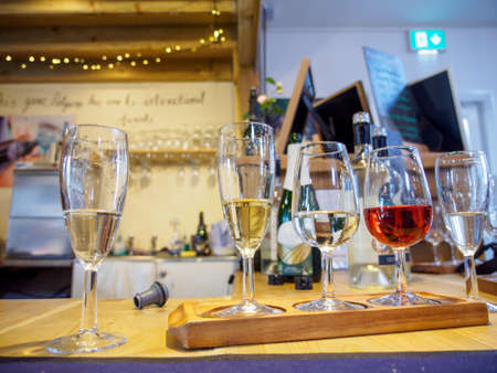 Wide closeup of multiple glasses of fine wines during a tasting session. Penzace, Cornwall, England. Travel and Cornish wine industry. Stock Photo