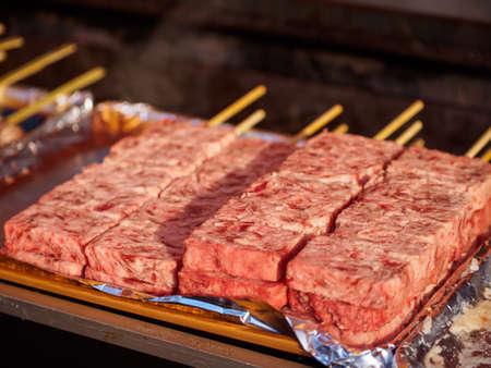 Closeup of raw beef on skewers at a Kushiyaki, grilled meats stand. Omiya, Saitama, Japan. Travel and street foods.