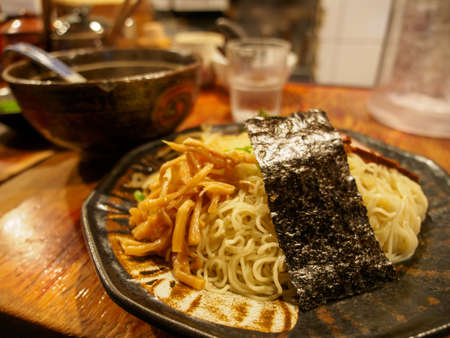 Wide closeup of Tsukemen ramen noodles, with bamboo sprouts. seaweed, and dipping sauce, on a restaurant counter. Nakano, Tokyo, Japan. Travel and cuisine.