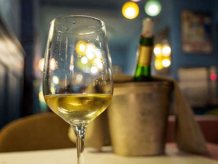 Closeup detail of a glass of Alsatian Reisling white wine at a romantic restaurant dinner. Shallow focus, bucket and chilled bottle in background. Colmar, France. Travel and cuisine. Stock Photo