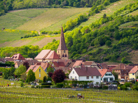 Wide view of the pariah crooked spire church of St. Gall and medieval houses of the valley village of Niedermorschwihr. Haut-Rhin, France. Travel and tourism. Stock Photo