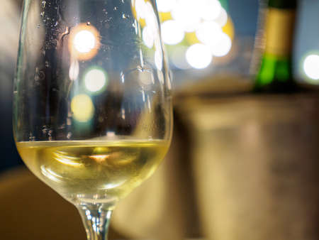 Macro closeup detail of a glass of Alsatian white wine at a romantic restaurant dinner. Shallow focus, bucket and chilled bottle in background. Colmar, France. Food and drinks. Stock Photo
