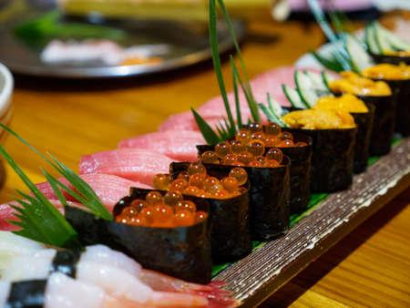 Closeup macro detail of a plate of Nigiri Sushi, with Bluefin tuna belly, salmon roe, and sea urchin, at a restaurant. Bangkok, Thailand. Japanese gourmet cuisine.