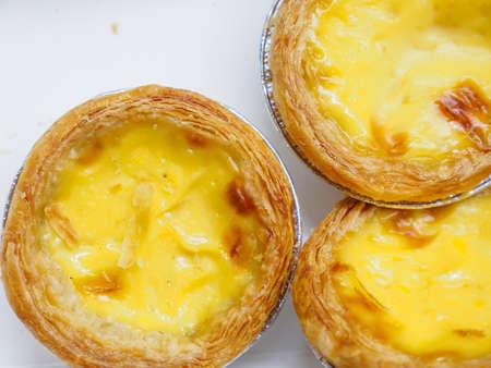 Closeup macro detail of multiple freshly baked egg tarts on a white background. Bangkok, Thailand. Desserts and cuisine.