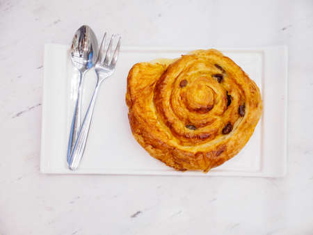 Closeup of a cinnamon roll on a ceramic plate with cutlery, on a marble tabletop. Bangkok, Thailand. Travel and desserts. Stock Photo
