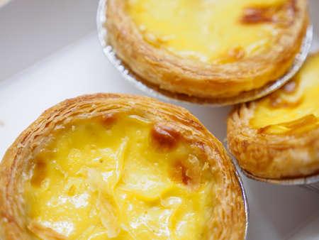Macro detail of multiple egg tarts at a bakery. Bangkok, Thailand. Desserts and sweets.