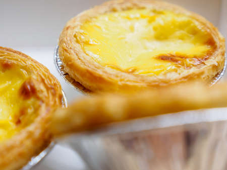 Macro closeup of egg tarts in a paper box, delivery from a bakery. Bangkok, Thailand. Travel and cuisine.