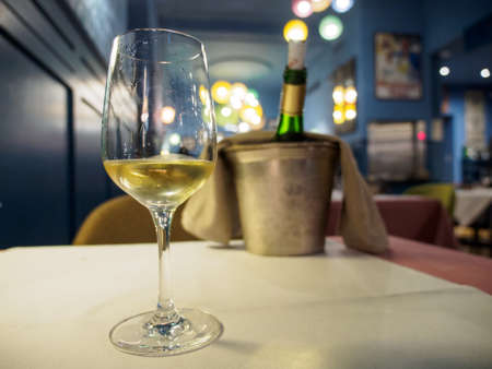 Wide closeup of a glass of Alsatian white wine as an aperitif at a romantic restaurant dinner. Shallow focus, bucket and chilled bottle on table in background. Colmar, France. Travel and cuisine.