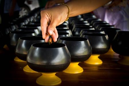 limosna: Mujeres que funcionan con monedas de Down en cuenco de las limosnas, los sucesivos en el trabajo de la manera en la religi�n budista
