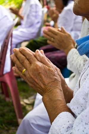 manos unidas: Manos de la abuela en el ritual budista en el templo de Tailandia
