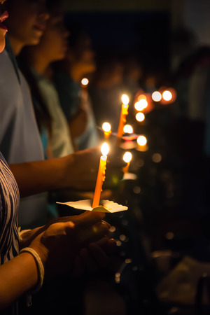 People hold candles light at night