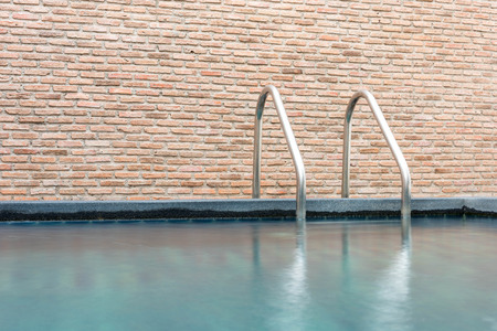 waterpool: Swimming pool with stairnice brick wall background