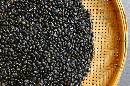 Black beans for background on bamboo Stock Photo