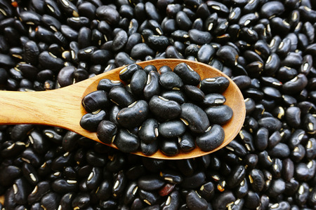 black beans: Black beans with a wooden spoon Stock Photo