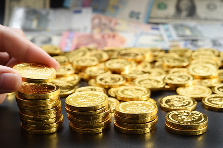 hand deliver a stack of coins in the form of graph on black background Stock Photo