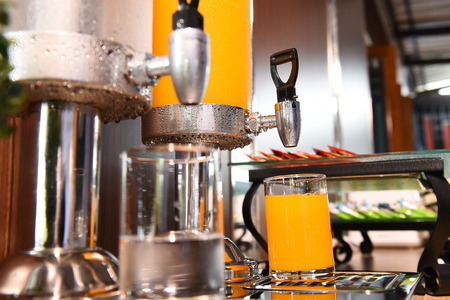 gallons: Orange juice and water in water cooler on table in the hotel Stock Photo