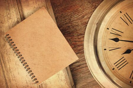 Closeup antique old style clock and notebook with sunlight vintage color