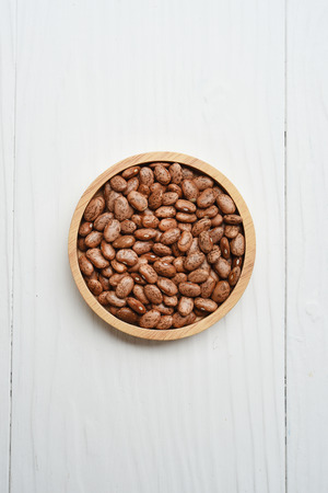 Pinto bean in wooden bowl on white background Stock Photo