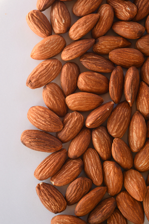 close up of almonds on white background