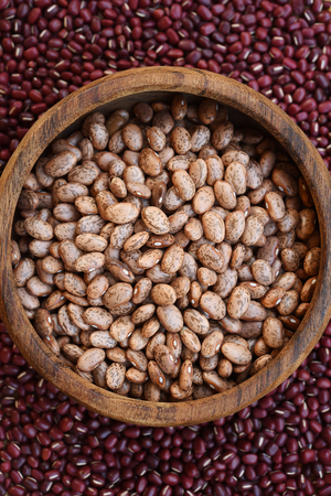 Pinto bean in wooden bowl on red bean background