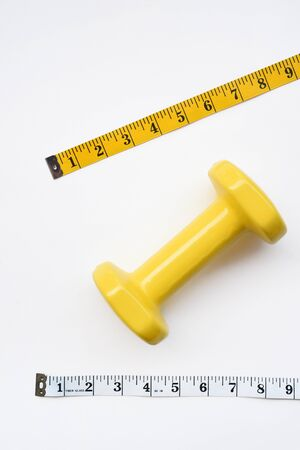 Fitness concept dumbbell and measuring tape isolated on white background