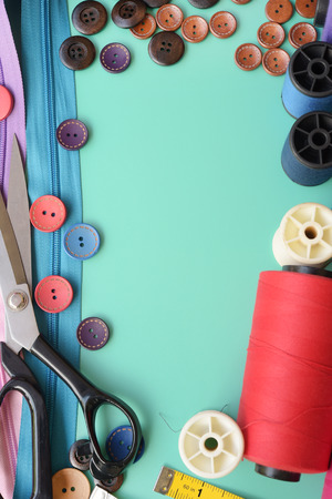 Composition with threads and sewing accessories on green background