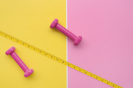 Fitness concept dumbbell and measuring tape for background Stock Photo