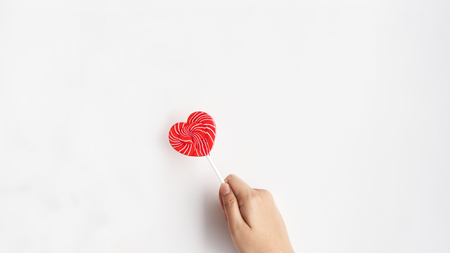 close up of heart lollipop on hand for background