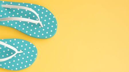 Blue flip flops on yellow background 스톡 콘텐츠