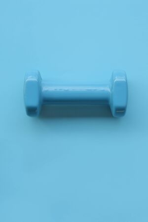 close up of dumbbell on blue background