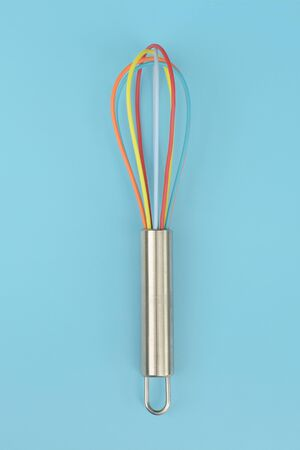 close up of colorful kitchen whisk on blue background Imagens