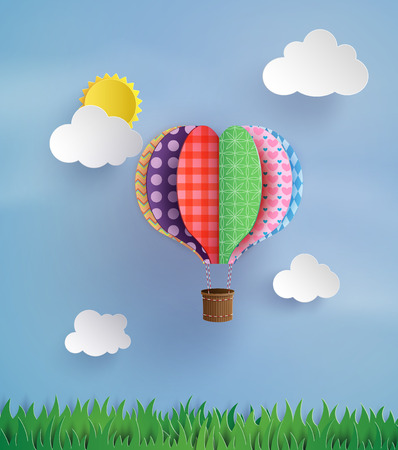 Origami made colorful hot air balloon fly over grass.paper art style.