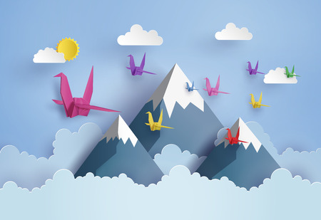 Origami made colorful paper bird flying on blue sky over mountain with cloud . paper art and craft style.