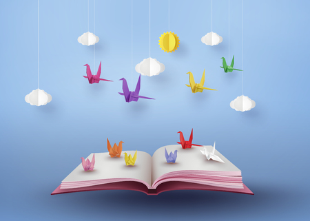 Origami made colorful paper bird flying over open book and blue sky with cloud . paper art and craft style.