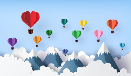 Origami made hot air balloon in a heart shape float over the mountain. paper art 3d from digital craft.