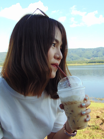 Beautiful women are sucking the coffee from the glass of coffee.