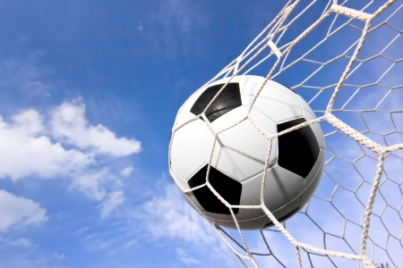 football object: close-up of a soccer ball (football) going into the back of the net with a blue sky background